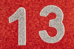 Number thirteen silver color over a red background. Anniversary. Stock Photos