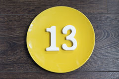 The number thirteen on the yellow plate. Royalty Free Stock Photography