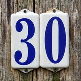 Number thirty - 30. House number thirty - 30 - against a wooden background stock image