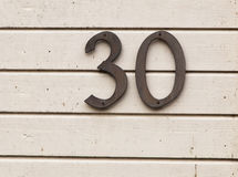 The number thirty. On a light painted house wall stock photo