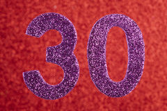 Number thirty purple color over a red background. Anniversary. Stock Photography