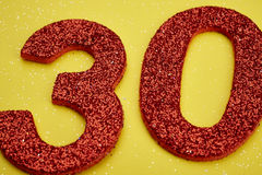 Number thirty red color over a yellow background. Anniversary. Royalty Free Stock Photo