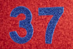 Number thirty-seven blue color over a red background. Anniversar Royalty Free Stock Photo