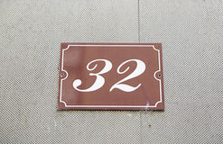 Number thirty-two on the wall of a house Stock Photos
