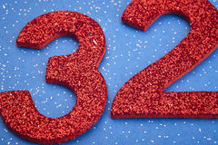 Number thirtytwo red color over a blue background. Anniversary. Horizontal Royalty Free Stock Images