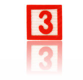 Number three. In an alphabet wood block on a reflective surface Royalty Free Stock Photography