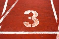 Number three on a athetics track Stock Photo