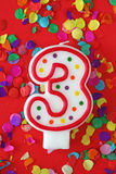 Number three birthday candle. On red background Stock Images