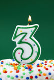 Number three birthday candle. On green background Stock Photo