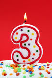Number three birthday candle. On red background Royalty Free Stock Photo