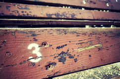 Number three painted on an old wooden seat. Royalty Free Stock Photography