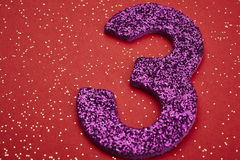 Number three purple color over a red background. Anniversary Royalty Free Stock Photos