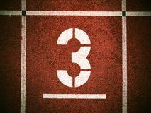 Number three. White track number on red rubber racetrack, texture of running racetracks in athletic stadium Stock Image