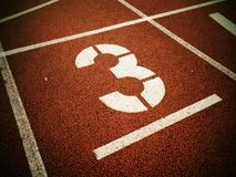 Number three. White track number on red rubber racetrack,. Texture of running racetracks in small stadium Royalty Free Stock Photos