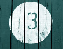 Number three on wooden cyan toned wall. Stock Image