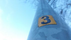 The number three on a lamppost. The number three in a yellow square on a lamppost Stock Photo