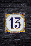 Number 13 tile. Decorative delftware tile with the number 13, on a black painted wall in Amsterdam Royalty Free Stock Photos