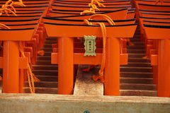 Number of tiny orange traditional Japanese gates (miniatures of Toriis) in the Shinto shrines Stock Photos