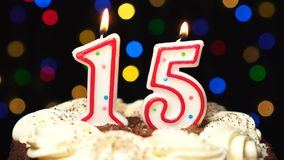 Number 15 on top of cake - fifteen birthday candle burning - blow out at the end. Color blurred background