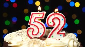 Number 52 on top of cake - fifty two birthday candle burning - blow out at the end. Color blurred background.  stock footage