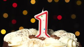 Number 1 on top of cake - one birthday candle burning - blow out at the end. Color blurred background