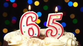 Number 65 on top of cake - sixty five birthday candle burning - blow out at the end. Color blurred background