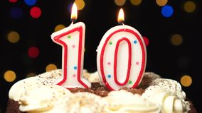 Number 10 on top of cake - ten birthday candle burning - blow out at the end. Color blurred background