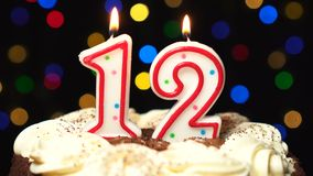 Number 12 on top of cake - twelve birthday candle burning - blow out at the end. Color blurred background.  stock footage