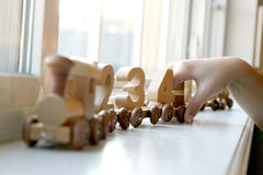 Number Train. Child's hand playing with wooden toy number train Royalty Free Stock Images