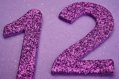 Number twelve purple color over a purple background. Anniversary. Horizontal Royalty Free Stock Image