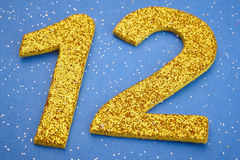 Number twelve yellow color over a blue background. Anniversary Royalty Free Stock Image
