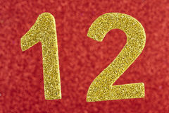 Number twelve yellow color over a red background. Anniversary. Stock Photos