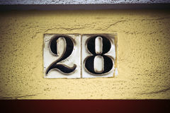 Number twenty eight in raised figures on plaster wall Stock Photos