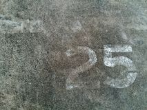 Number 25 Twenty five in white painted on the gray concrete wall or surface of street with copy space royalty free stock photography