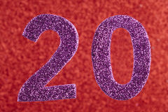 Number twenty purple over a red background. Anniversary. Stock Photos