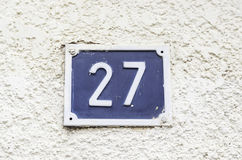 Number twenty.seven on a wall. Detail of an information signal, odd number Stock Image