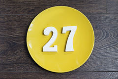 The number twenty-seven on the yellow plate. Figure twenty-seven at the plate yellow and brown background Royalty Free Stock Photography