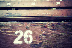 Number twenty six painted on an old wooden seat. Royalty Free Stock Photo