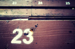 Number twenty three painted on an old wooden seat. Royalty Free Stock Image