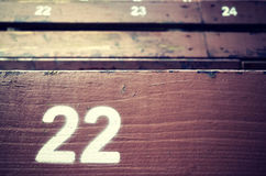 Number twenty two painted on an old wooden seat. Royalty Free Stock Images