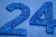 Number twentyfour blue color over a blue background. Anniversary Royalty Free Stock Photos