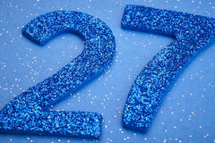 Number twentyseven blue color over a blue background. Anniversar Royalty Free Stock Photos