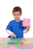 Number two. Five years old boy playing with colorful letters isolated on white Stock Photos