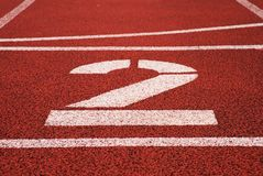 Number two. Big white track number on red rubber racetrack. Gentle textured racetracks in small stadium. Stock Photo