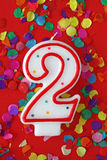 Number two birthday candle. On red background Royalty Free Stock Images