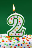Number two birthday candle. On green background Royalty Free Stock Photo
