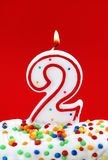 Number two birthday candle. On red background Stock Image
