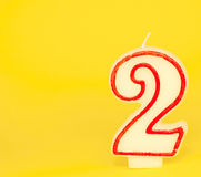 Number Two Candle on Yellow Background Royalty Free Stock Photos