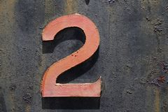 Number two metal on rust. A number 2 two made of steel that is a faded red colour mounted on a rusted steel background frokm a train Royalty Free Stock Photo