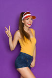 The Number Two. Smiling girl in orange shirt and sun visor showing two fingers or peace sign. Three quarter length studio shot on violet background Royalty Free Stock Image